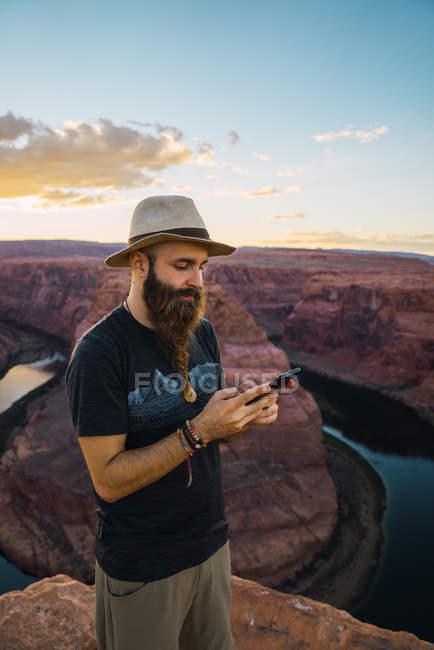 Schöner bärtiger Mann mit Hut auf dem Mobiltelefon, während er bei Sonnenuntergang an der Westküste von Usa vor der herrlichen Schlucht und dem Fluss steht — Stockfoto