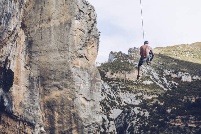 From below unrecognizable climber hanging on rope on rough cliff against blue sky — Stock Photo