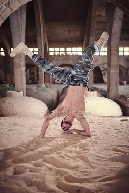 Macho novo sem camisa que executa o movimento moderno da dança na terra arenosa dentro da construção envelhecida — Fotografia de Stock