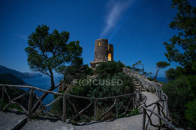 Lights from tower on top of high hill near sea and wonderful sky in evening — Stock Photo