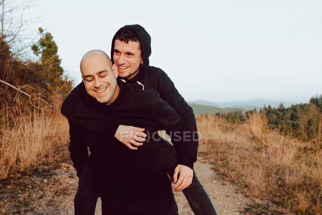 Happy homosexual couple having fun on route between plants in mountains — Stock Photo