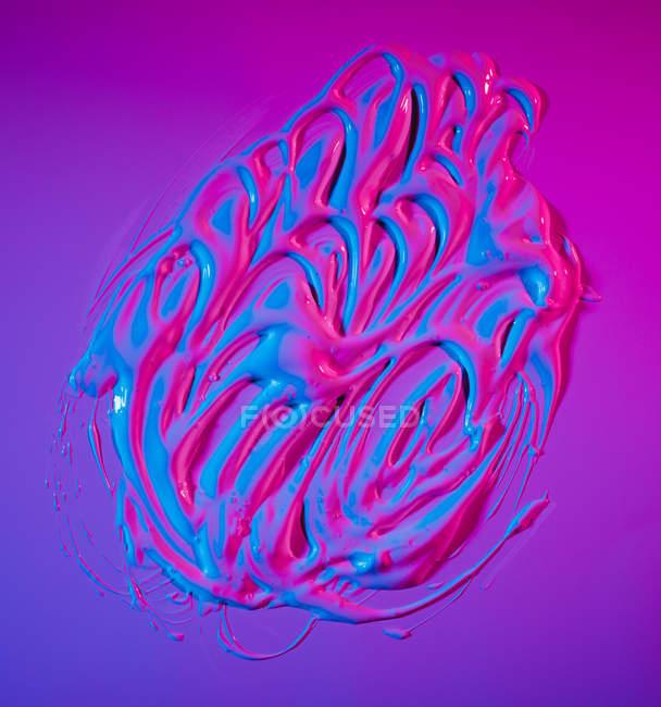 Pozzanghera di vernice acrilica al neon brillante diffusa su sfondo viola vivido — Foto stock