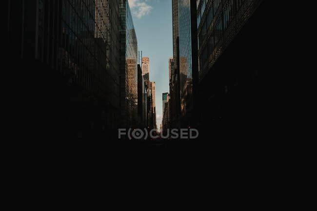 Vista panoramica sulla strada scura tra i grattacieli di vetro lucido alla luce del sole, New York — Foto stock