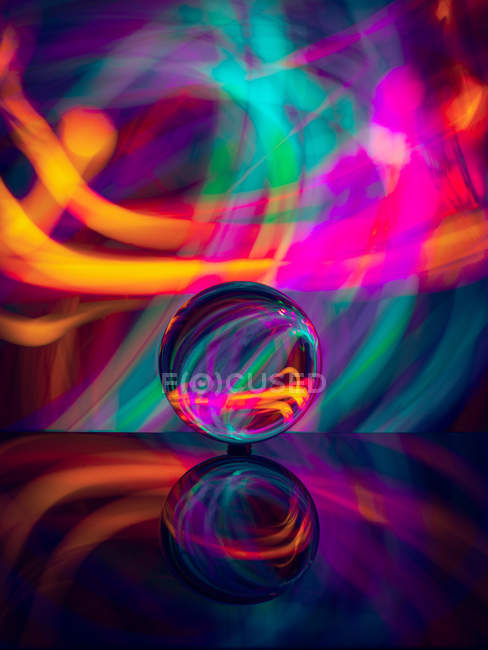 Crystal ball on surface with reflection near abstract shines — Stock Photo