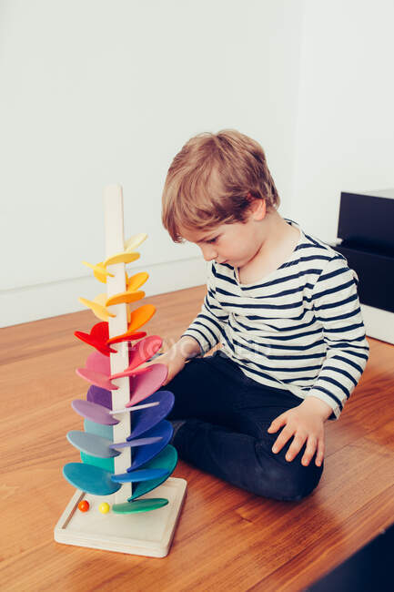 Blonde cute boy playing with waldorf sounding tower with marbles — стокове фото