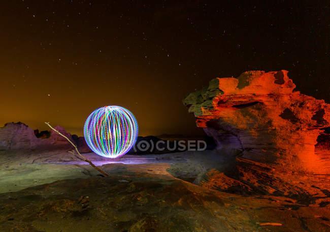 Абстрактна сфера, що знаходиться над скелями та чорним небом з зірками вночі — стокове фото