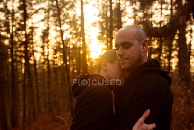 Романтическая гомосексуальная пара с закрытыми глазами обнимая в лесу в вечернее время — стоковое фото