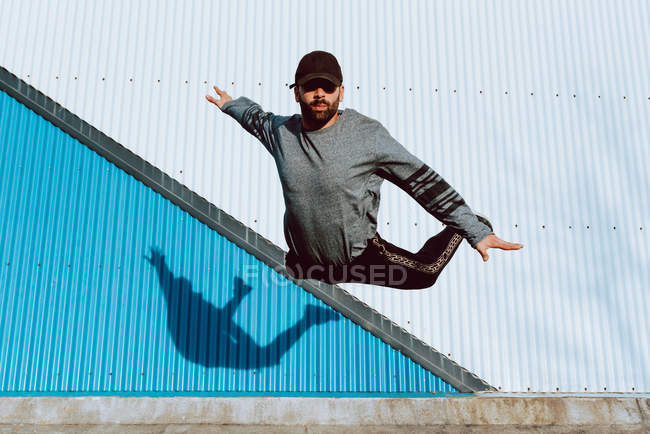 Guy in stylish outfit performing flip near wall of modern building on city street — Stock Photo