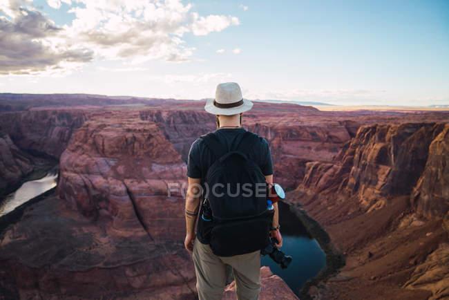Вид сзади парня с рюкзаком, держащего фотокамеру у красивого каньона и спокойной реки в солнечный день на Западном побережье США — стоковое фото