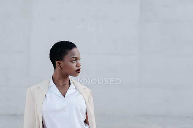 Élégant à la mode à poil court femme ethnique en tenue blanche posant contre le mur gris — Photo de stock