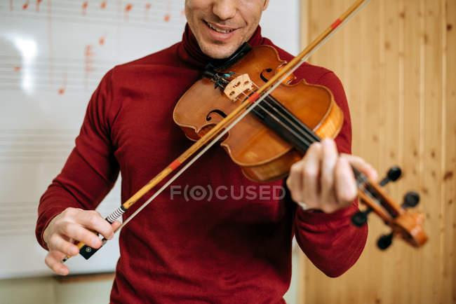 Junger Mann spielt Geige mit Schreibtafel im Hintergrund im Musikstudio — Stockfoto