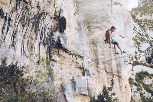 Dal basso di arrampicatore appeso su corda su ruvida scogliera contro cielo blu — Foto stock