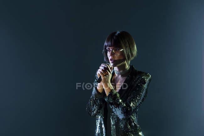 Mujer con estilo cantando en el escenario - foto de stock