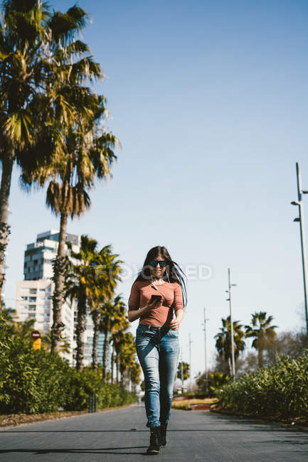Teen girl walking happily through the streets of the city on a sunny day — стокове фото