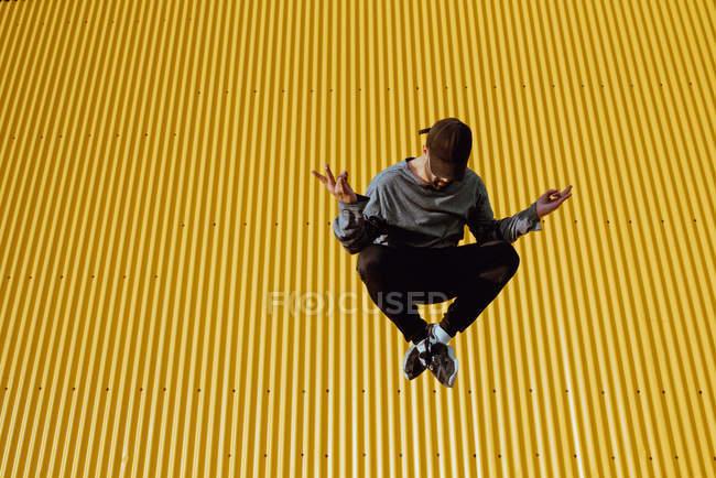 Bello ragazzo barbuto in abito alla moda saltando contro il muro giallo dell'edificio moderno — Foto stock