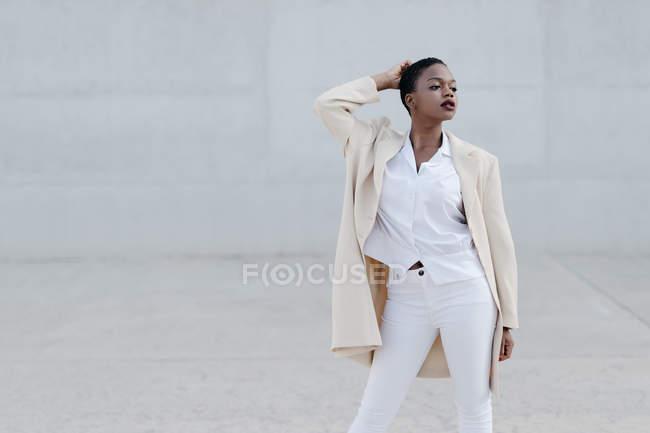Moda modelo de cabelos curtos em roupa branca posando contra a parede cinza — Fotografia de Stock