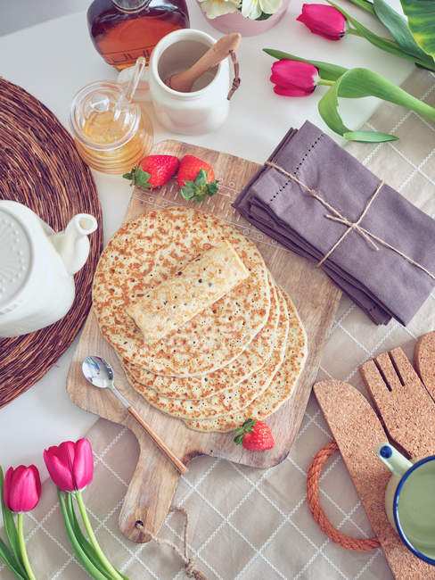 Breakfast with pancakes and strawberries on kitchen table with flowers — Stock Photo