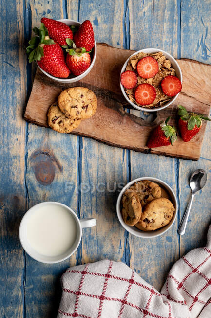 Glass and bottle of milk and pile of fresh cookies on wooden board near napkin — Stock Photo