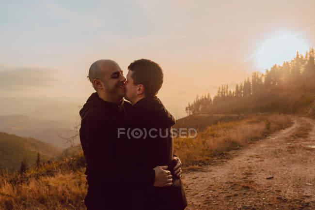Glückliches homosexuelles Paar umarmt und küsst sich an sonnigem Tag auf Waldweg — Stockfoto