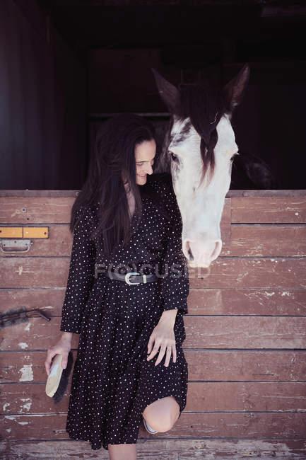 Donna attraente in piedi vicino a cavallo in stalla — Foto stock