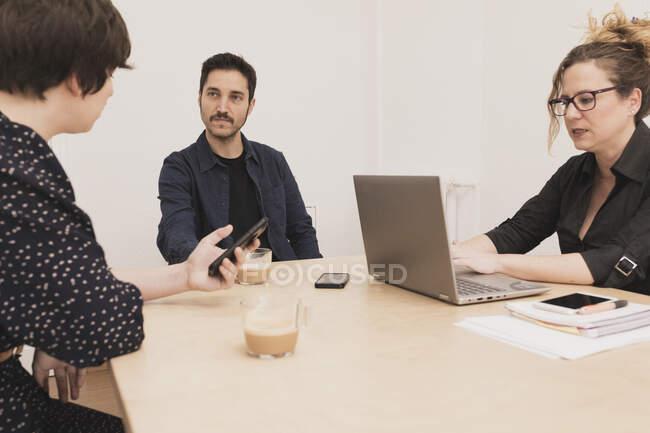 Concentrato giovane maschio vicino alla signora navigando sul telefono cellulare e digitando sul computer portatile al tavolo in ufficio — Foto stock