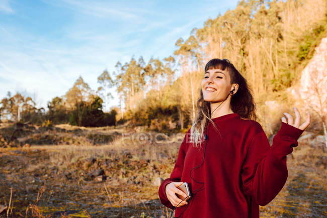 Young smiling hipster woman listening music with mobile phone in nature — Stock Photo