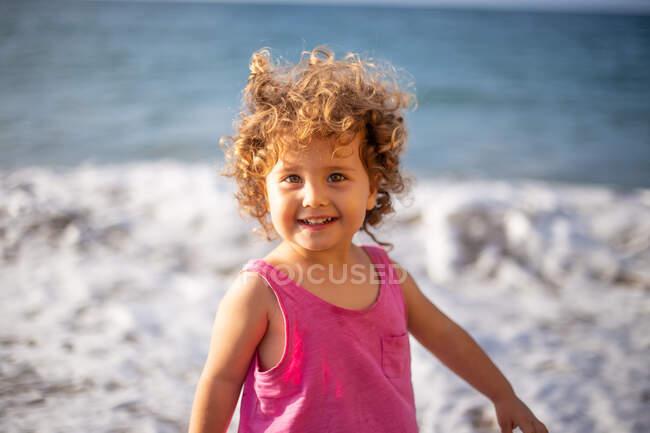 Ragazza divertente sulla spiaggia di sabbia vicino all'acqua con schiuma e spruzzi in estate — Foto stock