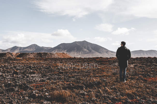 Back view of young male tourist hiking in barren landscape with stone hills on background in Lanzarote, Canary Islands, Spain — Stock Photo