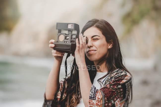 Вдумлива молода жінка, беручи фото з камерою на березі на розмитому фоні — стокове фото