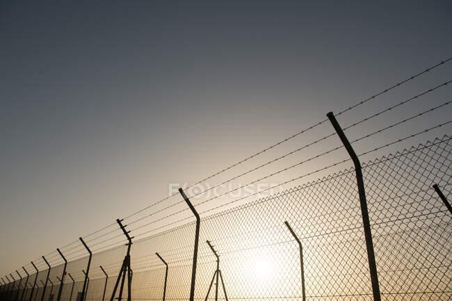 Cerca de segurança metálica localizada na frente do céu sem nuvens com sol brilhante — Fotografia de Stock