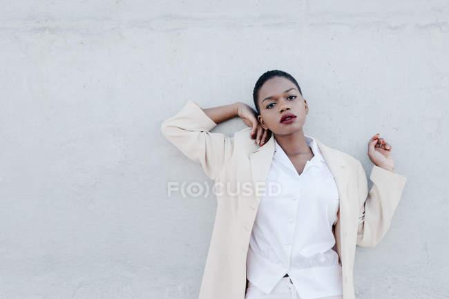 Мода короткий волоссям модель в білому Екіпіровка що створюють проти сірої стіни — стокове фото