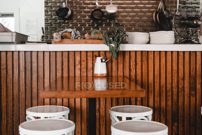 Wooden table with cutlery and stools near kitchen in cafe — Stock Photo