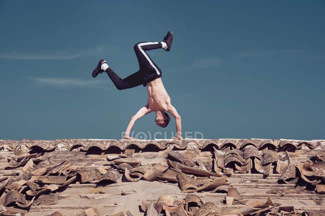 Человек, стоящий на крыше на фоне голубого неба — стоковое фото