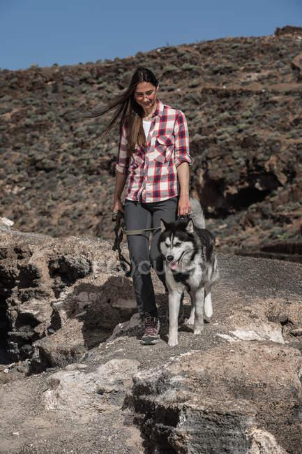 Giovane donna sorridente che cammina con husky su terreni deserti a Tenerife, Isole Canarie, Spagna — Foto stock