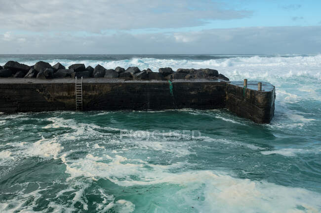 Breathtaking view of amazing stormy sea waving near weathered stony pier on cloudy day — Stock Photo