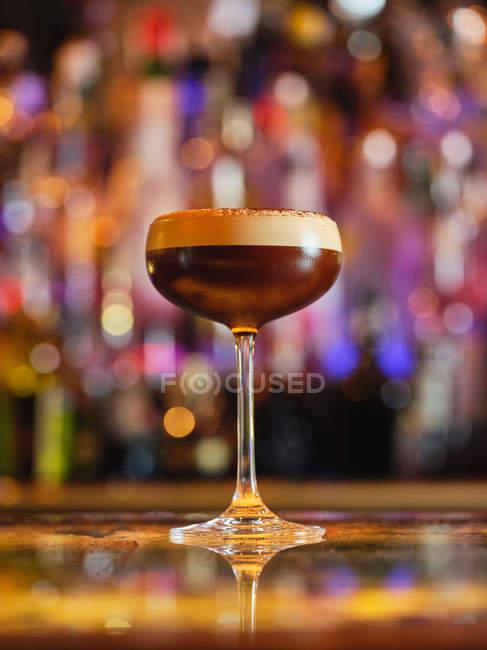 Скляне скло з смачним шоколадним коктейлем, поміщеним на лічильнику в сучасному барі. — стокове фото