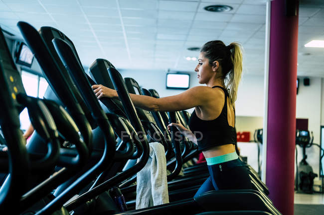 Pretty woman on exercise machine in gym — Stock Photo