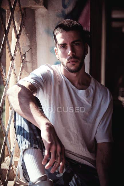Красивый молодой парень в модном наряде, смотрящий в камеру, сидя возле потрепанного окна в старом здании в солнечный день — стоковое фото