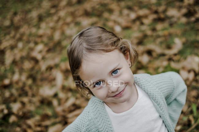 Retrato de niña positiva mirando a la cámara sobre fondo borroso en la naturaleza - foto de stock