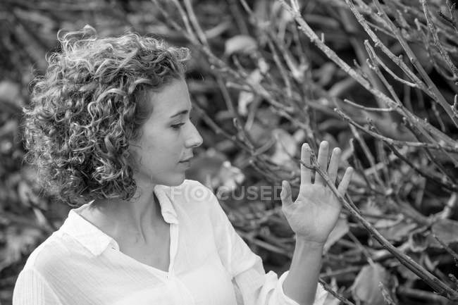 Young dreamy woman touching dry branches of shrub on blurred background — Stock Photo