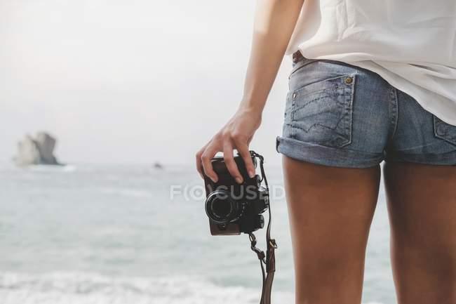 Visão traseira da mulher com câmera de foto retro em pé na praia e olhando para a vista do mar — Fotografia de Stock