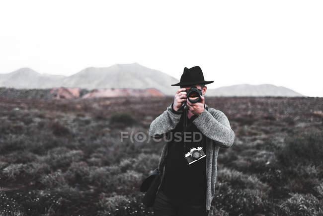 Junge männliche Touristen fotografieren mit der Kamera in Feld in lanzarote, Kanarischen Inseln, Spanien — Stockfoto