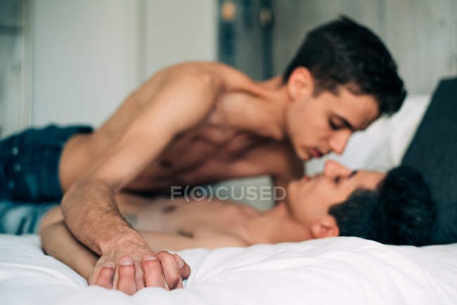 Passionate sexual happy shirtless gay couple in an intimate moment in the bed at home — Stock Photo