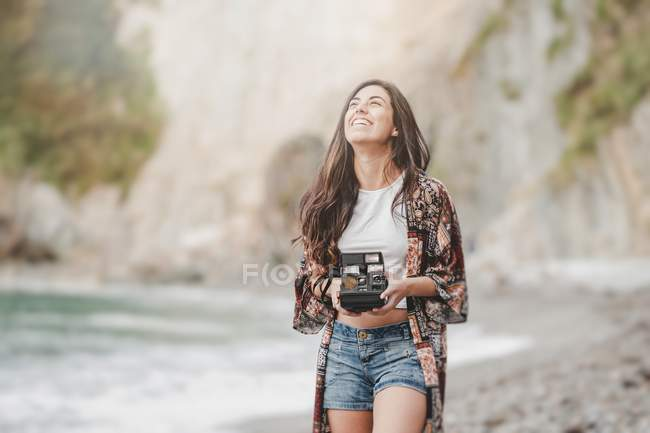 Улыбающаяся молодая женщина с камерой на берегу моря — стоковое фото