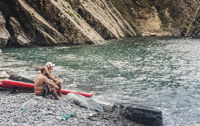 Thoughtful couple sitting on rocky shore near paddleboards and admiring view of majestic sea — Stock Photo
