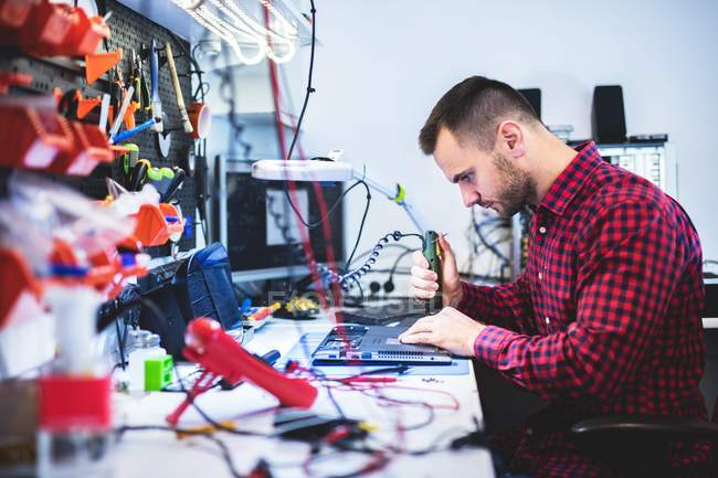 Uomo concentrato riparazione scheda madre sul posto di lavoro — Foto stock