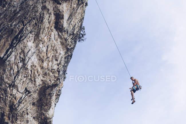 Знизу альпініст звисає на мотузці на нерівній скелі до блакитного неба. — стокове фото