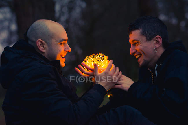 Homosexual couple with illuminated fairy lights sitting in murk forest in evening — Stock Photo
