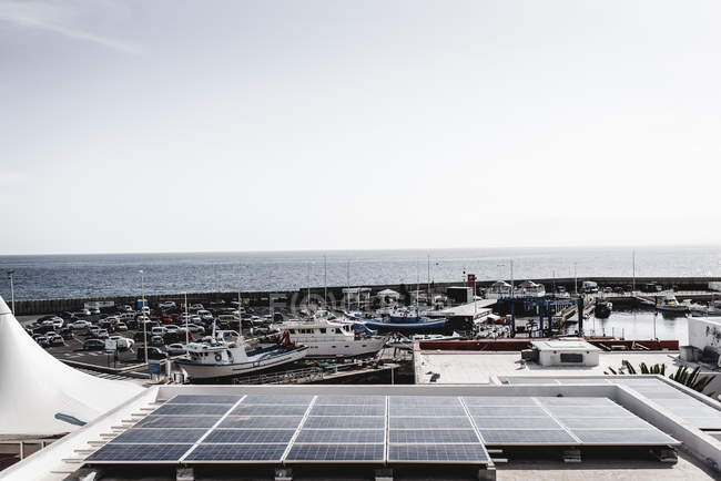 Solar battery on roof of house near ships and parking on seashore in Lanzarote, Canary Islands, Spain — Stock Photo