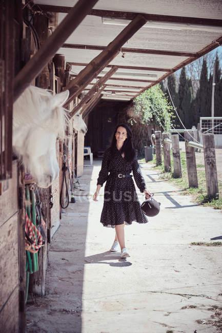 Привлекательная женщина, идущая рядом с лошадью в стойле — стоковое фото